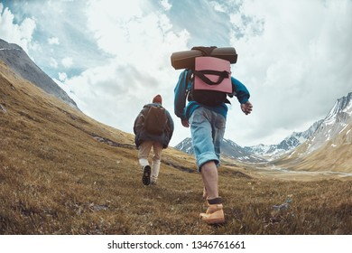 Two hikers in casual clothes and backpacks goes uphill in mountains