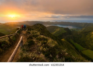 two hikers enjoying a spectacular view at sunset on the Azores