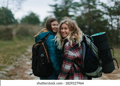 two hikers girls are walking on the road