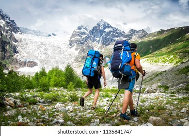 Two hikers with large backpacks in mountains. Tourists hike on rocky mounts. Leisure activity on mountain trek. Adventure of men in wild Svaneti region of Georgia. Groupe Hiking