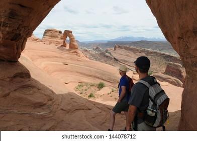 Two hikers look towards Delicate Arch in Moab, Utah.