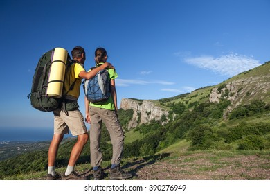 Two hikers looking at the mountain. Backpackers research a way at the mountains