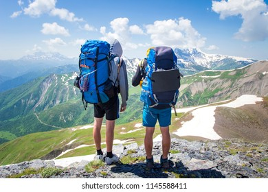 Two hikers in mountains with backpacks on sunny summer day. Mountain trek in Svaneti, Georgia. Tourists on peak of highland look at snowy mountains on blue sky background. Beautiful view on Caucasus