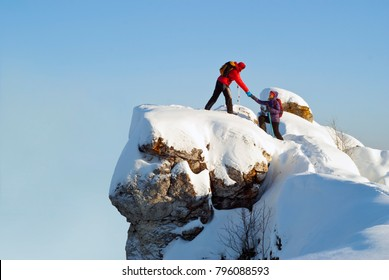 two hikers on top of the mountain in winter; a man helps a woman to climb a sheer stone