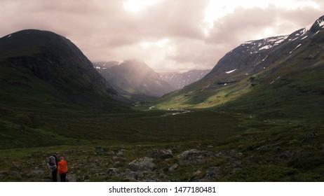 Two hikers overlooking a scenic valley in Sweden (Abisko)