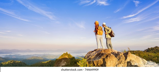 Two hikers relaxing on top of the mountain and enjoying valley view. Banner edition.