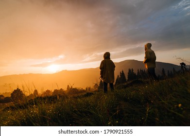 Two hikers stand in the rain on a meadow in the mountains and watch the incredible orange sunset. Two hikers in raincoats and sunset in the rain on a background of beautiful landscape.