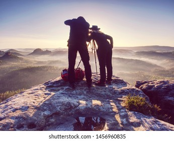Two hikers taking pictures and talk on top of the mountain. Hikers photographers with photo gear relaxing on top of a mountain and enjoying the view of valley