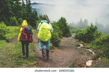 Two hikers tourist in raincoat walking on trail to green mountain forest in the fog with the yellow backpack in rainy weather.