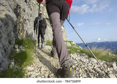 Two hikers  with trekking poles walking to the top