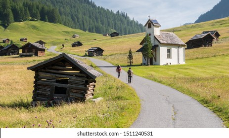 Two hikers walking on the road across the Tschey Meadows next to the chapel and hay barns, in Pfunds, Tyrol, Austria