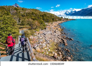 Two hikers and walking path at Lago Argentino near huge Perito Moreno glacier in Patagonia in golden Autumn, South America, sunny day, blue sky