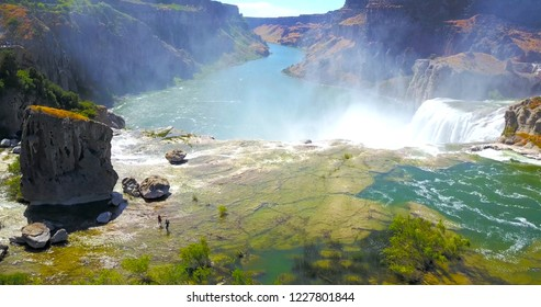 Two Hikers In Water On Top Of Shoshone Falls Idaho, Looking Out Over The River Canyon - USA
