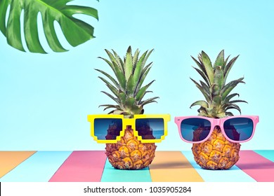 Two Hipster fashionable Fruits in Trendy Sunglasses, on Beach. Tropical fun Pineapple Couple. Bright Summer Color. Fashion Style. Creative Art. Party pineapple Mood,  funny summertime concept