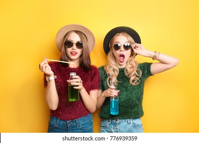 Two hipster girls with drinks on color background