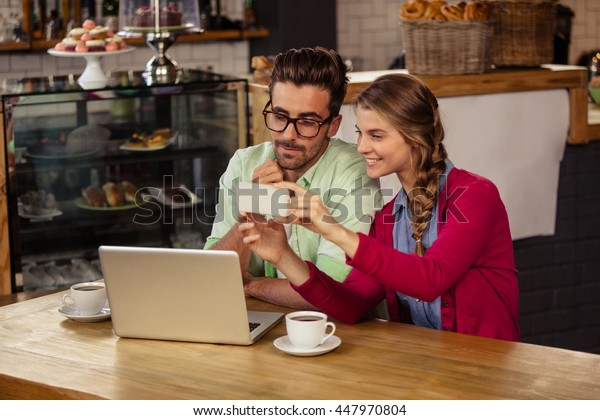 Two hipsters friends looking at smartphone at coffee shop