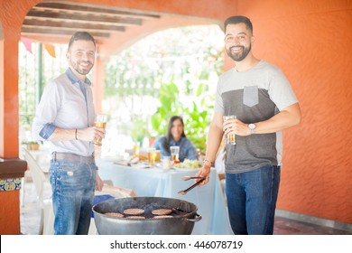 Two Hispanic guys having a good time while grilling hamburgers and drinking beers at a patio