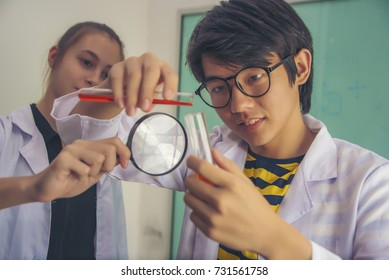 Two Hispanic scientist mixing chemicals and holding Magnifying glass in lap