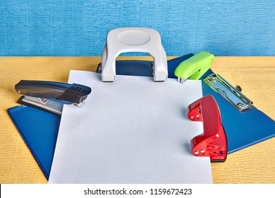 Two hole puncher and two staplers lie over office folder with a spring clip or clipboard and the empty sheet of white paper with copy space, mockup for design.