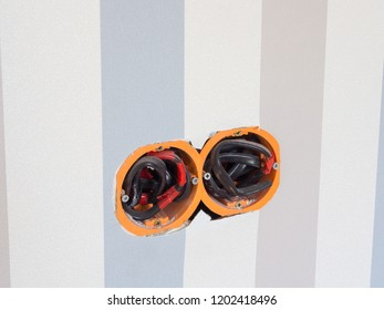 two holes in the wall with electrical wires to connect sockets