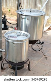 Two home brew kettles boiling wort with propane tank