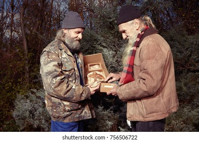 Two homeless older men celebrating christmas in park with bread and butter