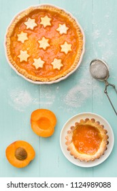 Two homemade apricot cakes on turquoise wooden background.