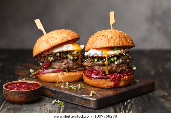 Two homemade beef burgers with mushrooms, micro greens, red onion, fried eggs and beet sauce on wooden cutting board. Side view, close up