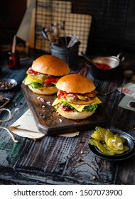 two homemade burgers with fried chicken, lettuce, cheese, onion, pickled cucumbers, ketchup on board stands on dark wooden table with bowl of veggies, pepper, vintage plates, bottles. selective focus