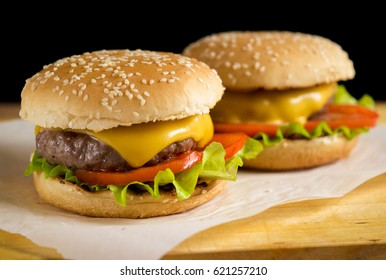 Two homemade burgers with grilled beef and cheese on paper