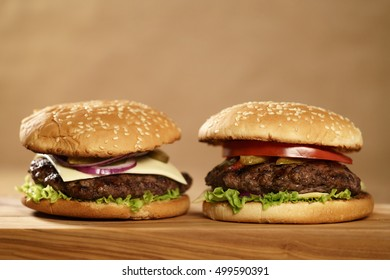 two homemade burgers on olive board on oak table