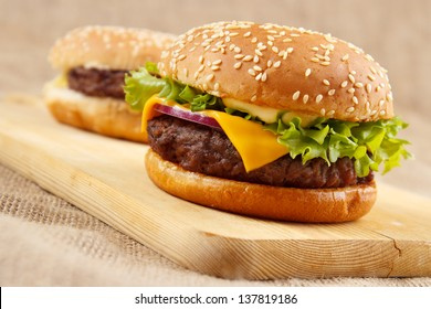 Two homemade grilled hamburgers on wooden board
