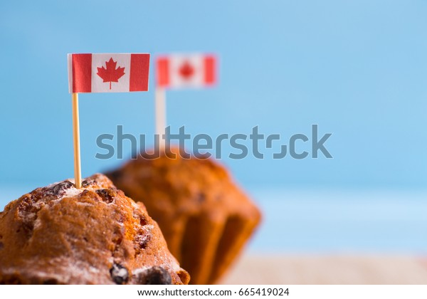 Two homemade muffins with little Canadian flag on blue background. Canada day card. 1 July cakes.