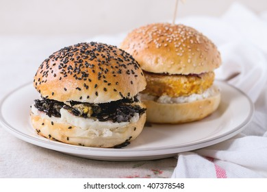 Two Homemade veggie burgers with sweet potato and black rice, served on white plate with kitchen towel over white textured background.