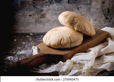 Two homemade wholegrain pita bread on wooden cutting board, served with flour over dark table.