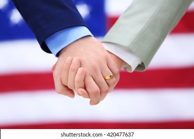 Two homosexuals holding hands on American flag background
