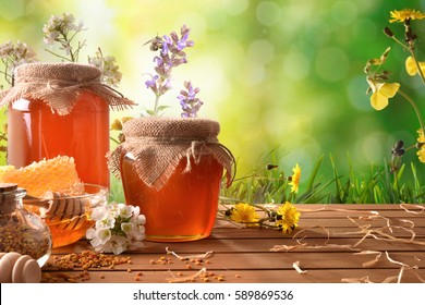 Two honey pots with honeycomb and bee pollen on a wooden table and green nature background with flowers. Front view. Horizontal composition