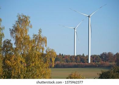 Two horizontal axis wind turbines in autumn farmlands