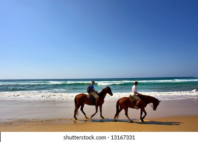 Two horse riders on beach. Shot in Sodwana Bay Nature Reserve, KwaZulu-Natal province, Southern Mozambique area, South Africa.