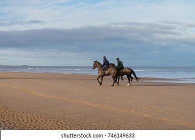 Two horse riders on the beach at Holkham / North Norfolk on a bright, sunny morning.
