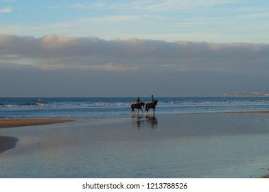 Two horsemen riding on the beach of Deauville