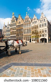Two horses add charm to the front facades of the famous medieval Guild Houses and Cobblestone Grote Markt Square of Antwerp, Belgium on a clear sunny, blue sky day. Vertical copy space