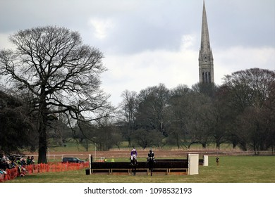 Two horses jump the last fence at the Holderness Hunt Point To Point overlooked by South Dalton Church Spire : Dalton Park, East Yorkshire, UK : 15 March 2105 : Pic Mick Atkins