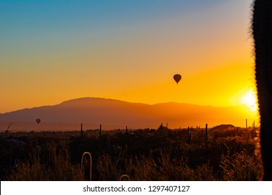 Two hot air balloons drifting along at sunrise over the Sonoran Desert near Saguaro National Park by Marana and Tucson, Arizona. Mountains, a colorful sky and cactus at dawn. Beautiful colors. 2019.
