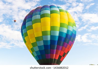 Two hot air balloons floating under vibrant blue sky with puffy