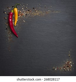 Two hot chili peppers with different spices on a dark stone slab with copyspace.