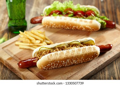 Two hot dogs with french fries on wooden cutting board. Junk food