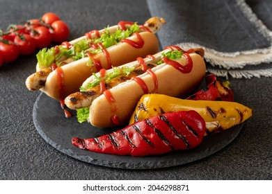 Two hot dogs with grilled sausages on stone board