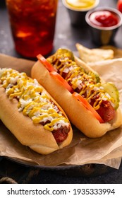 Two hot dogs with ketchup and mustard on parchment paper