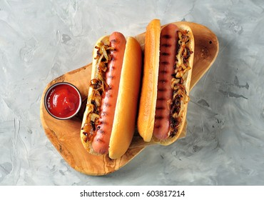 Two Hot dogs on an olive serving board with crispy onion and ketchup.